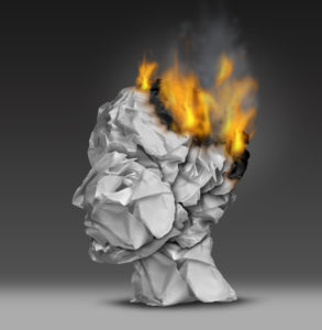 Headache  and mental illness concept as a group of crumpled office paper shaped as a human head that is on fire burning away at the brain as a symbol and medical metaphor for emotional stress at work or degenerative dementia disease as alzheimers.